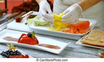 Hands quickly break colorful bread. Cooking board with...