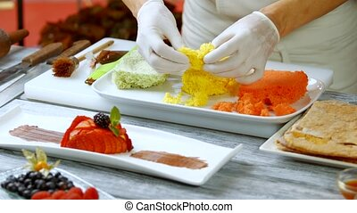 Man's hands break colorful bread. Dessert on long white...