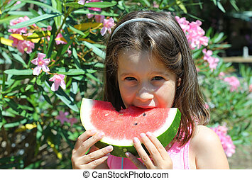 cute little girl with long brown hair eating a slice of...