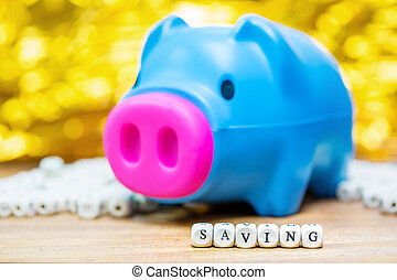 Blue piggy bank with Saving message on white bokeh...