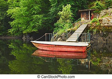 Red boat on the river - Wooden pier and red boat on the...