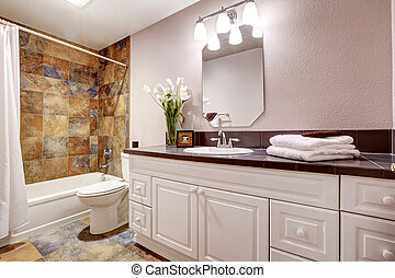 Bathroom with white cabinets and title floor