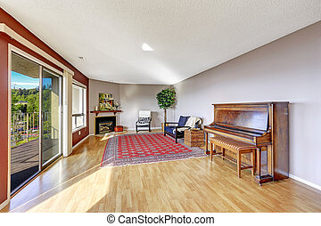 Living room with hardwood floor, fireplace, piano and rug.