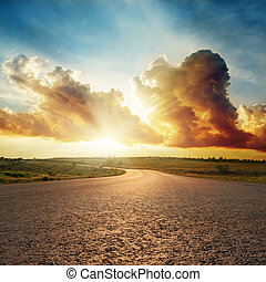 sunset in dramatic clouds over asphalt road