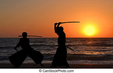 Men silhouettes practicing Aikido at sunrise