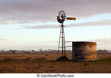 Windmill at sunrise on a farm with a water dam