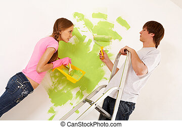 Painting wall - Industrious couple looking at each other...