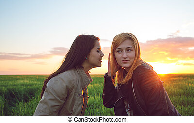 people communication and friendship concept- Two girl friends whispering secrets