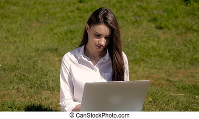 Portrait of Cute Student Girl Working With Laptop In Park of...