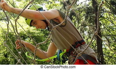 Man climbing in Adventure Park - Man climbing the trees in...