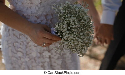 Man and woman holding hands. Bride hold bouquet of wild...