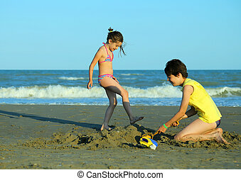 little girl and her brother play with water in the beach in...