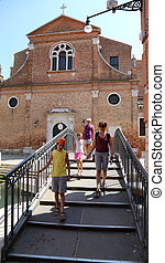 family of tourists on the bridge next to a church in the...