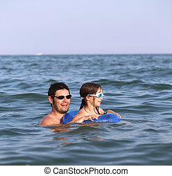 Happy family with father and daughter playing in the sea in...
