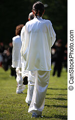 fans of martial arts Tai Chi with white silk dress during...