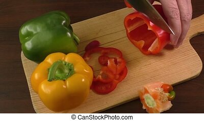 Cutting and preparing bell peppers on a cutting board,...