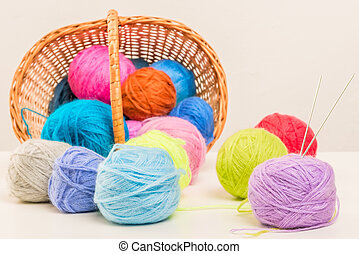 colored woolen thread crumbled from wicker basket close up...