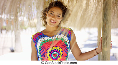 Woman under thatch beach umbrella - Beautiful smiling woman...