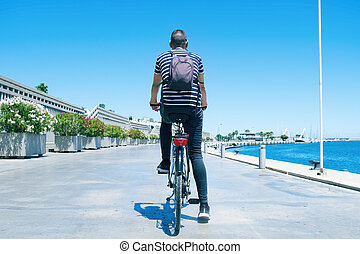 man cycling by the port of Valencia, Spain