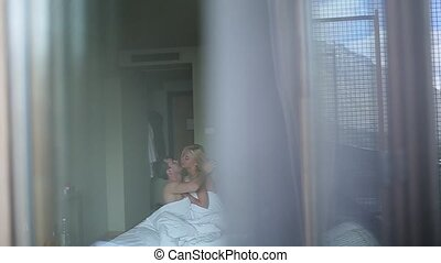 Couple embracing lying on their bed