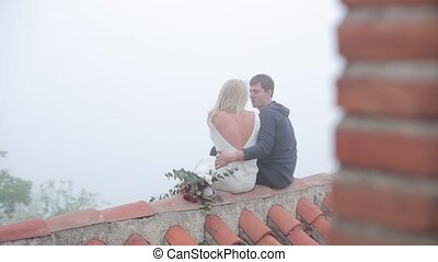 Couple sitting on the roof with red slate.