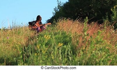 Happy young girl playing guitar outdoors. Rays of the...