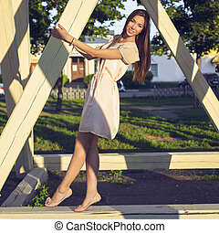 Happy brunette woman in a dress relaxing fun in the park leaning on wooden piles in the  enjoy your vacation, fashion style urban life. Smiling girl bright summer day.