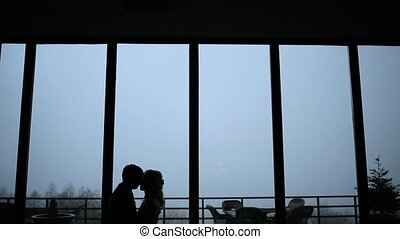 Couple kissing on the background of big panoramic windows and fog