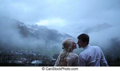 Couple kissing on the background of mountains