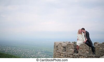 Couple sitting on the edge on the background of valley