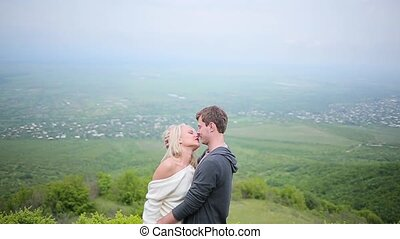 Couple kissing on the background of valley