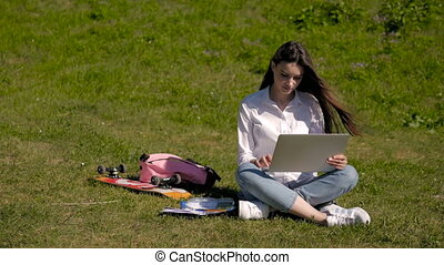 Young Pretty Hipster Student Girl Using Laptop In a Park, Net Surfing Outdoors