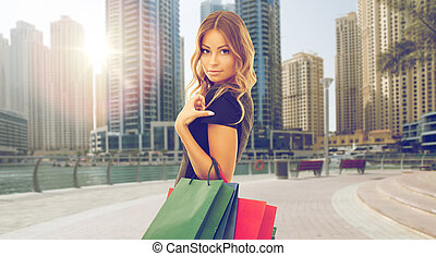 happy woman with shopping bags over dubai city - people,...