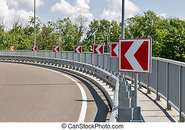 road signs, indicating left turn - white arrows on red road...