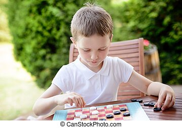 Little boy playing checkers board game