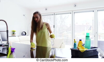 Spring Cleaning - A young woman is cleaning a counter top in...