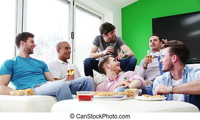 Men Enjoying Pizza And Beer - Group of men sat at home...