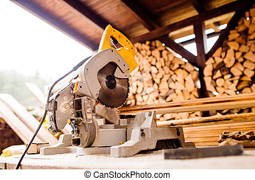 Circular saw laid on table, stack of wood behind it - Close...
