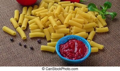 Raw yellow pasta, macaroni on sack background