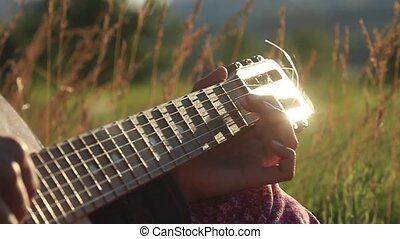 Happy young girl playing guitar outdoors Rays of the setting...
