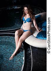 Beautiful young blonde caucasian woman in bikini relaxing in...