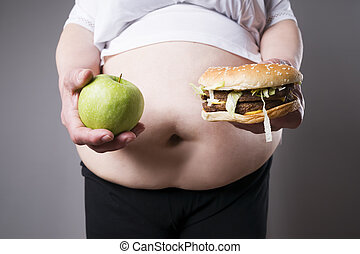 Fat women suffer from obesity with big hamburger and apple in hands, junk food concept