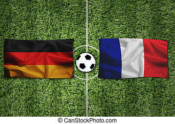 Germany flag Vs frace flag and ball on green grass.