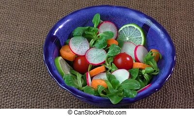 Bowl of fresh vegetable salad on jute table cloth