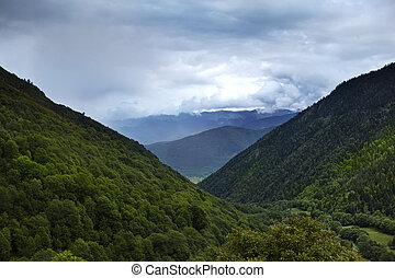 Trees on moutains - Mountains and cloudy sky in Pyrenees,...
