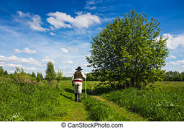 Man in black hat with a stic climbs the slope of a green...