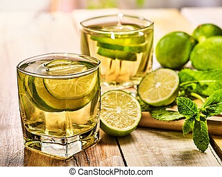 On wooden boards is glass with green transparent drink. -...
