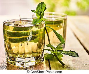 In cafe is glass with mohito green drink and lime. - Alcohol...