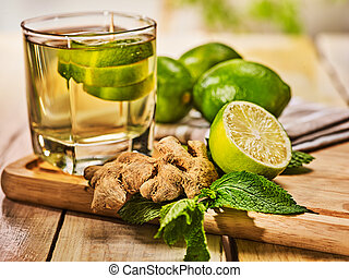Glass with green transparent lime drink and ginger . -...