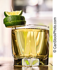 On wooden boards is glass with green drink and lime. -...